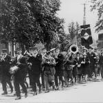 Nationaal Hengelconcours 'De Vriendenkring' werd door de harmonie begeleid in de optocht naar het water. Foto genomen voor het gemeentehuis in 1930,