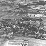 Luchtfoto van Malden met op de achtergrond het kanaal genomen in 1939. De rijksweg loopt van links naar rechts met uiterst links de aansluiting van de Dorpsesteeg, de huidige Groesbeekseweg. Uiterst rechts de Kloosterstraat met het Klooster en Mariaschool (het Honk), het gemeentehuis, de St. Jozef school en het partyhouse het 'Jachthuis'.